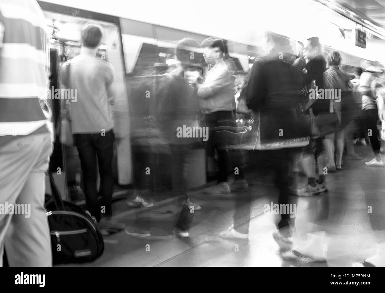 Motion blur people walking in and out the train in train station - Stock Image