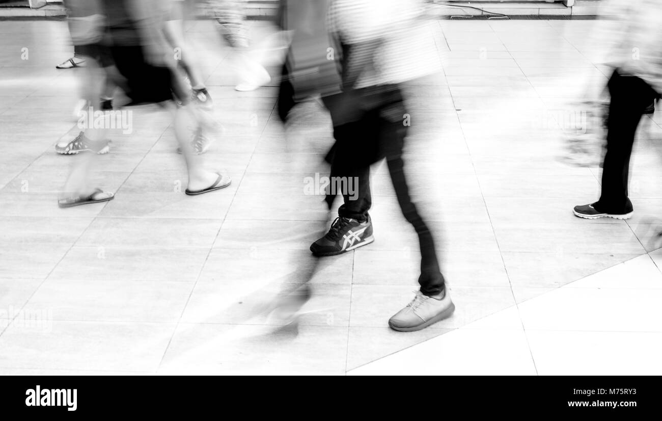 Motion blur people walking in fashion mall - black and white filter - Stock Image