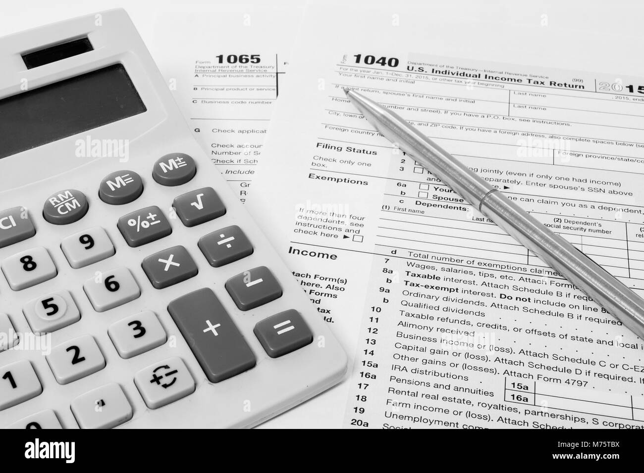 form 1065 calculator  US tax form 14 and 14 with a pen and calculator Stock ...