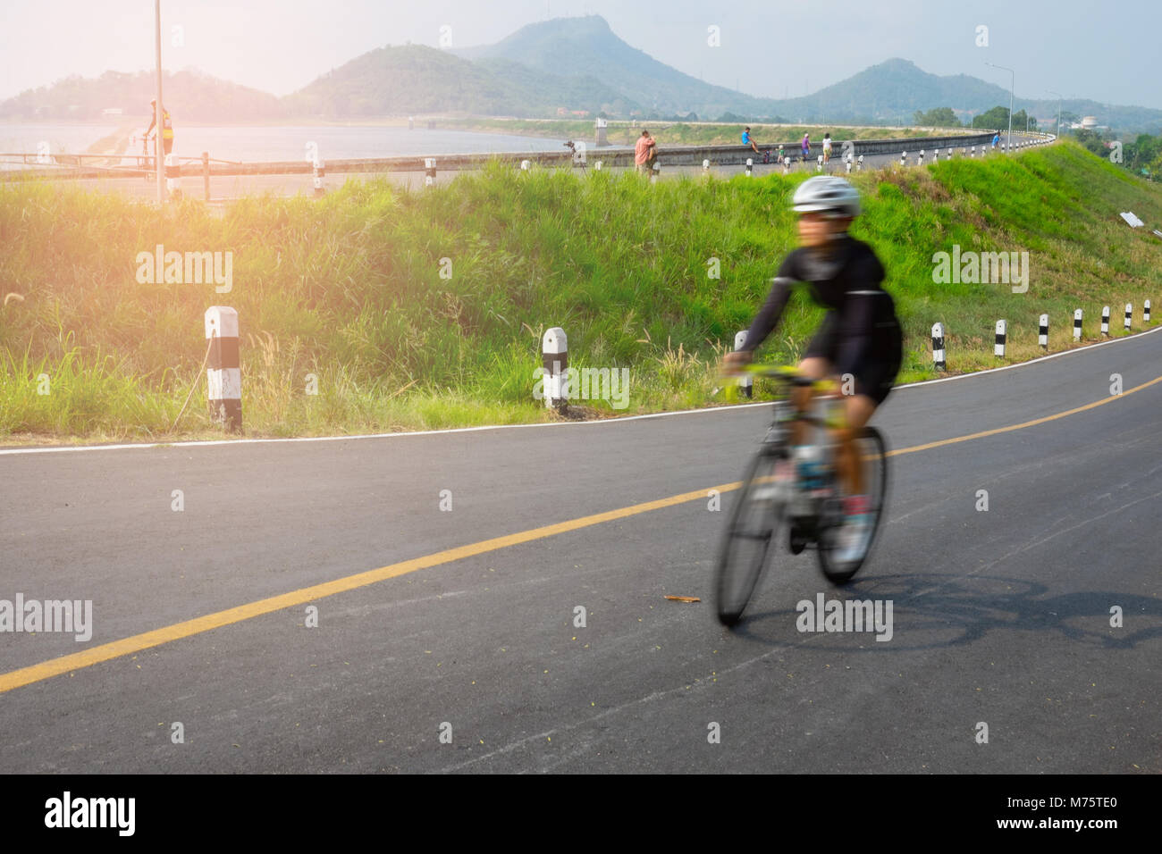 Motion blur woman riding bicycle along the lake side road in Thailand - Stock Image