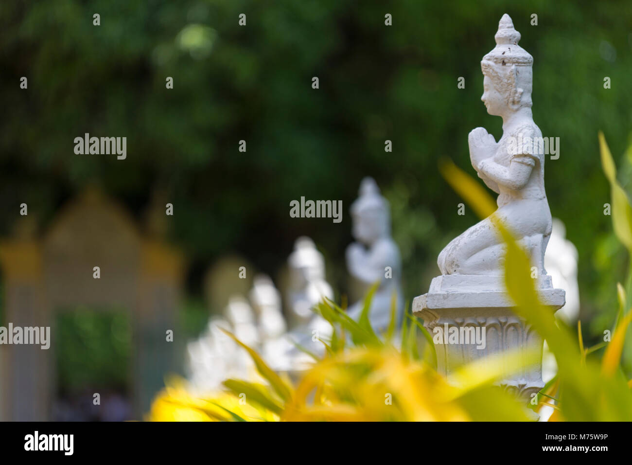 Multiple White Buddhist Statue With Clapsed Hand In Green Garden