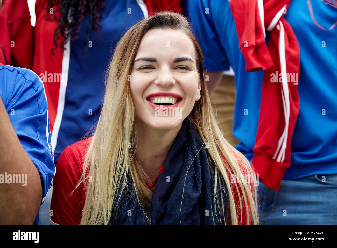 Woman watching football match, smiling cheerfully - Stock Image