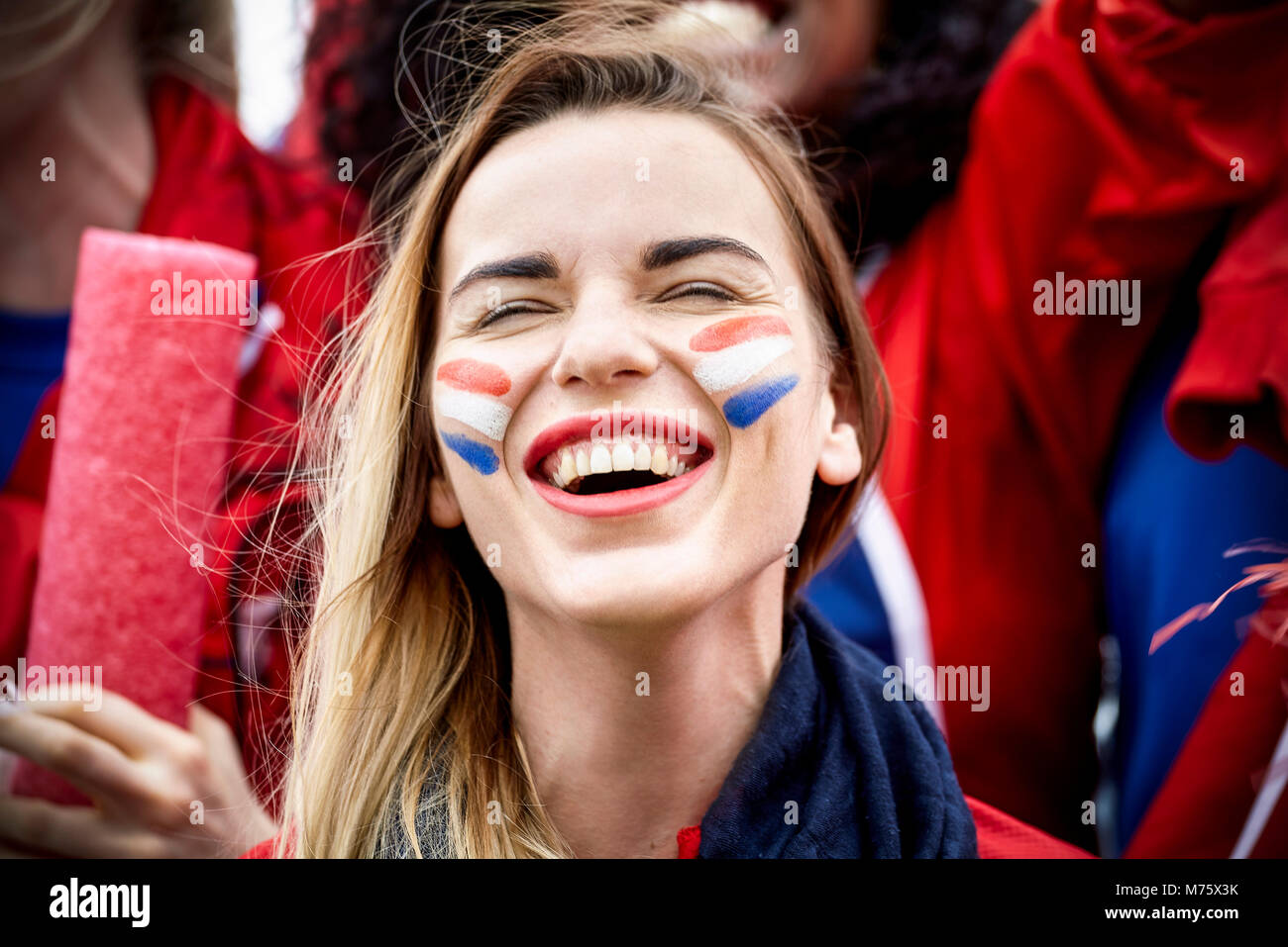 French football fan smiling at match, portrait - Stock Image