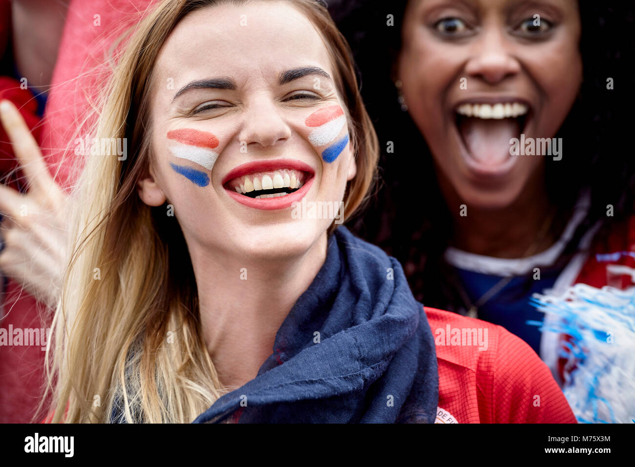 French football fans smiling and cheering at match - Stock Image