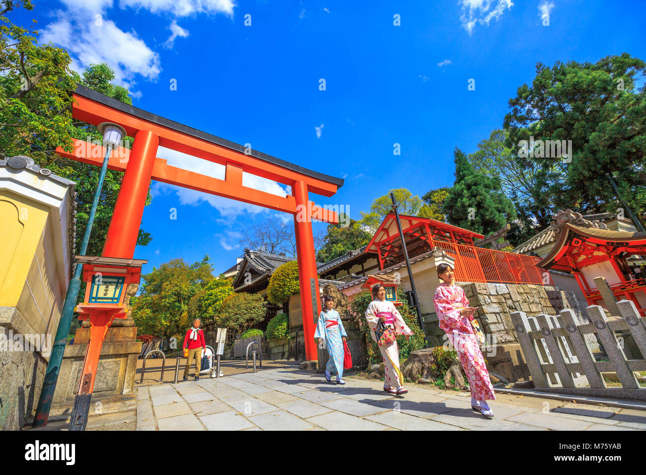 Kyoto, Japan - April 24, 2017: Japanese women with kimono at red Torii Gate of Yasaka Shrine in spring season. Gion - Stock Image