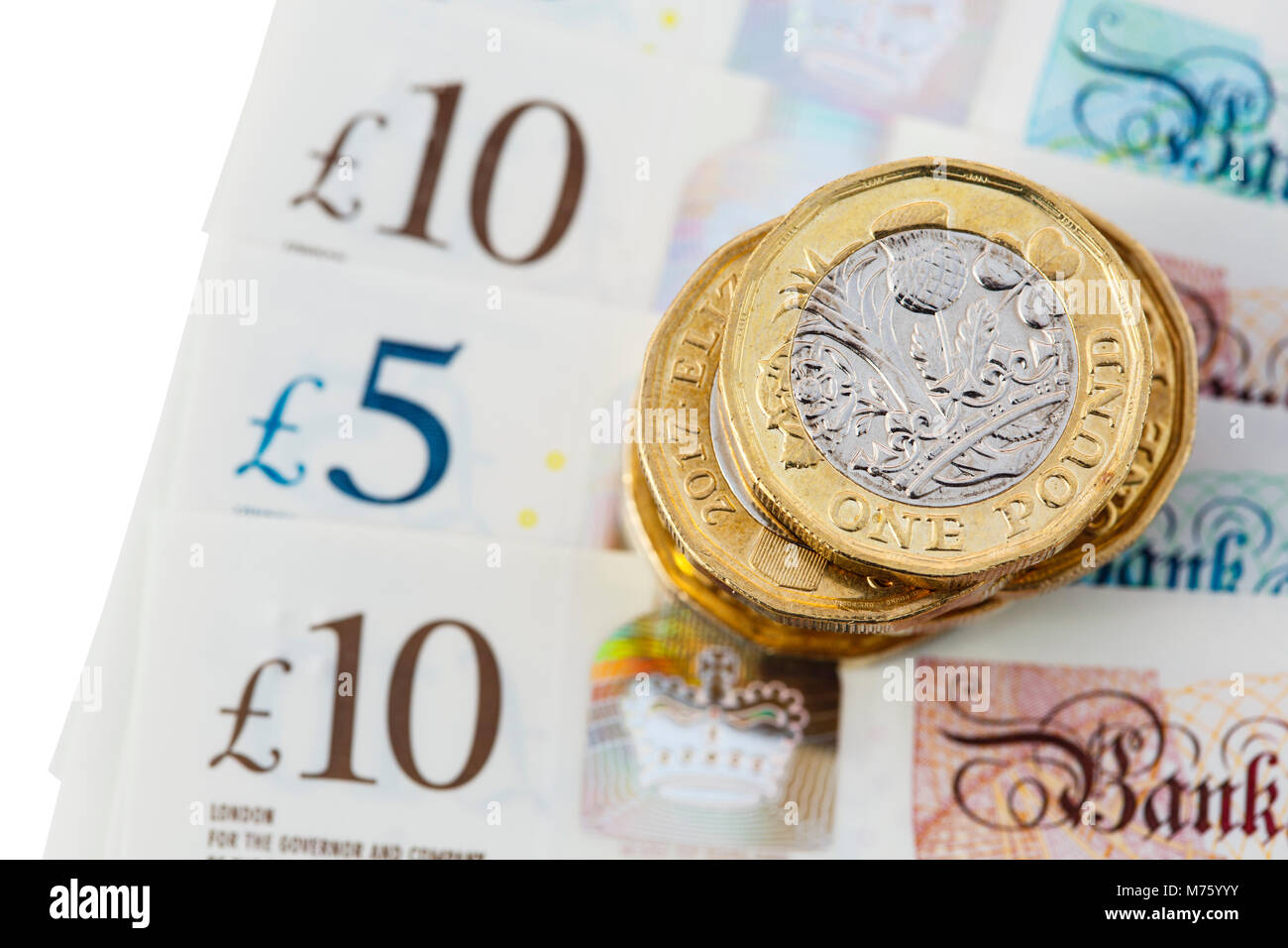 Pile of British 12 sided one pound coins money sterling pounds on new polymer £10 and £5 notes GBP close - Stock Image