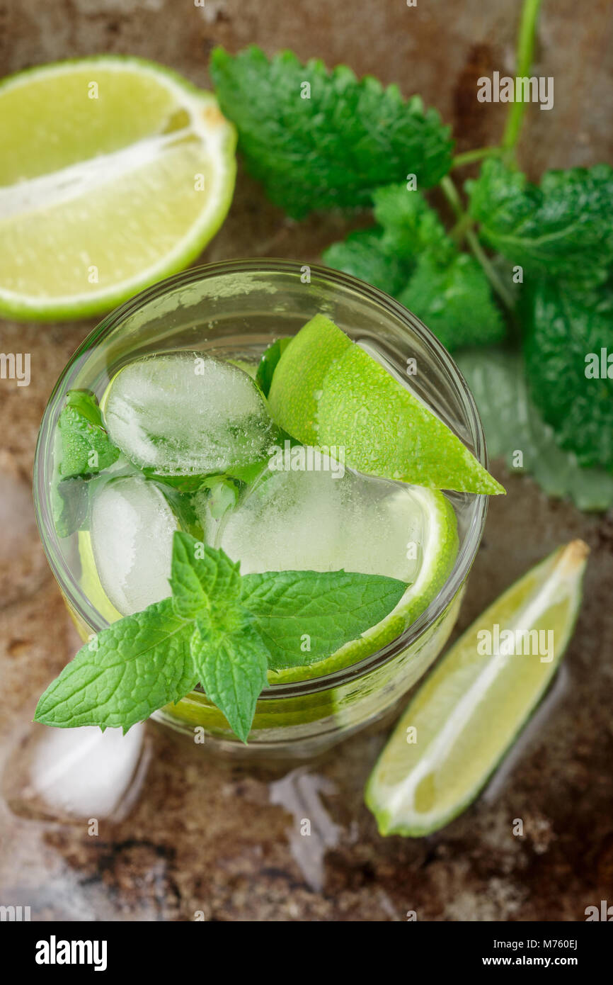 Mojito cocktail or lemonade with lime, mint and ice cubes. Traditional summer refreshing drink. Selective focus - Stock Image