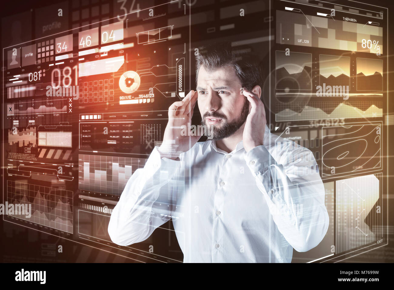 Worried man touching the temples while thinking about his mistake - Stock Image