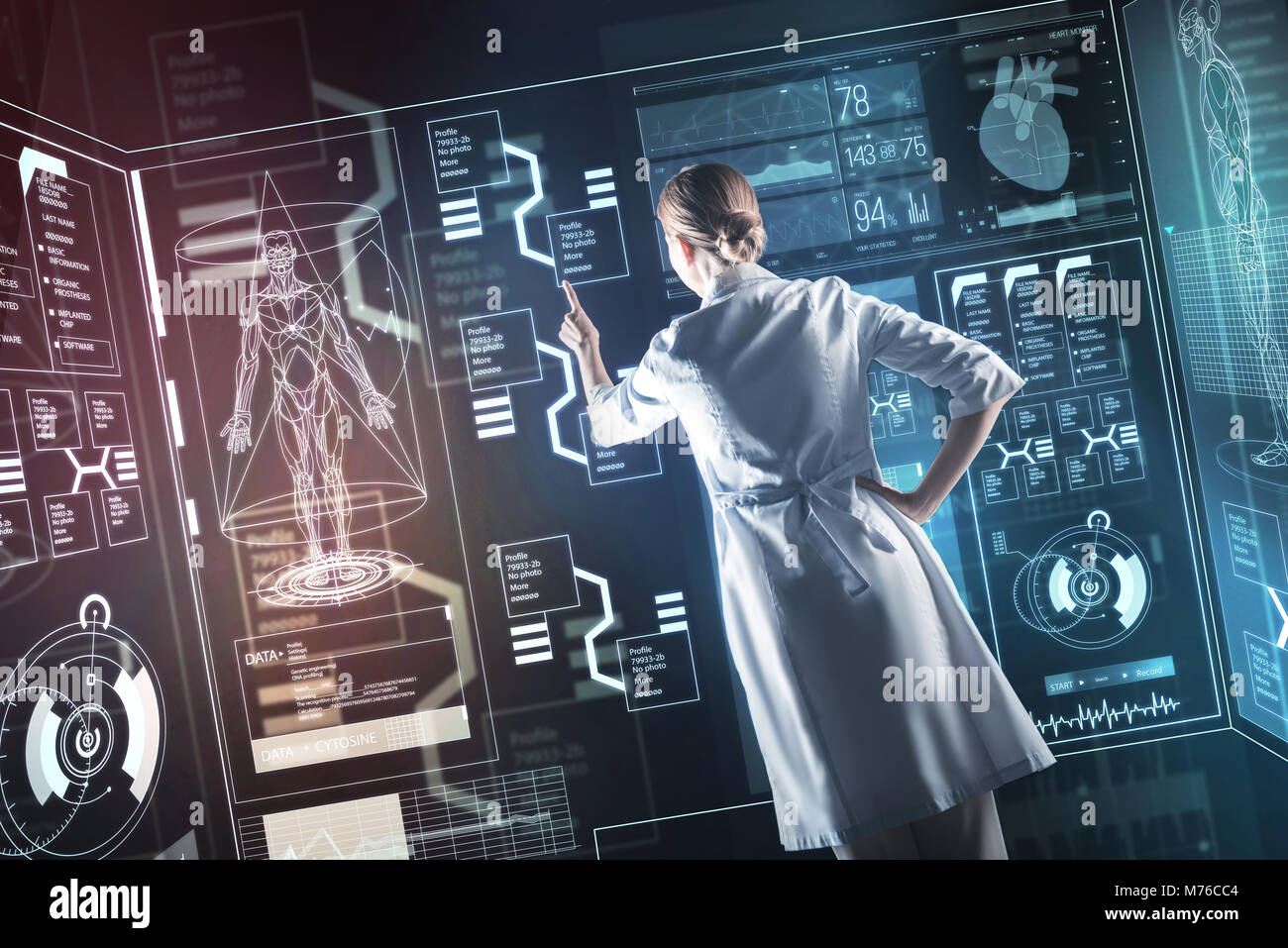 Progressive doctor pointing to the transparent screen while working - Stock Image