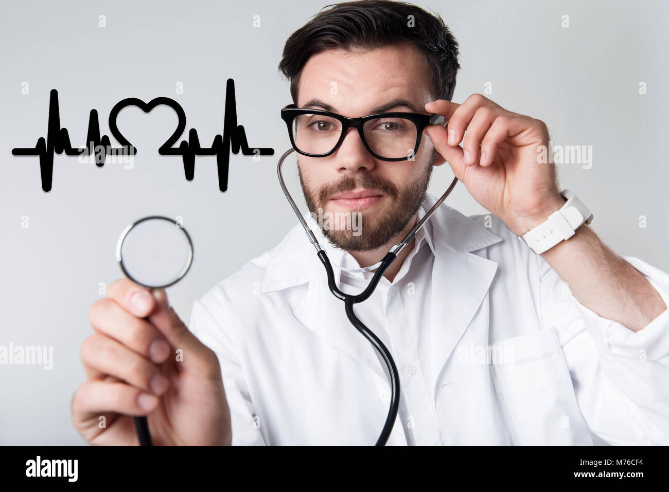 Smart cardiologist holding a stethoscope while examining his patient - Stock Image