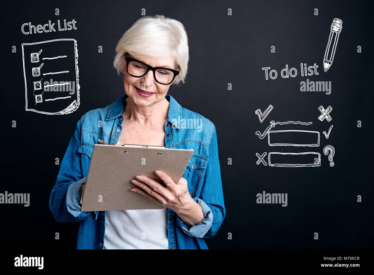 Mature woman holding a clipboard and looking at her list - Stock Image