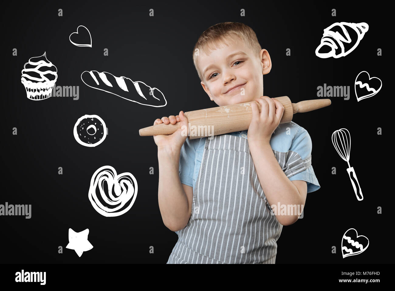 Positive boy dreaming of becoming a cook and holding a rolling pin - Stock Image
