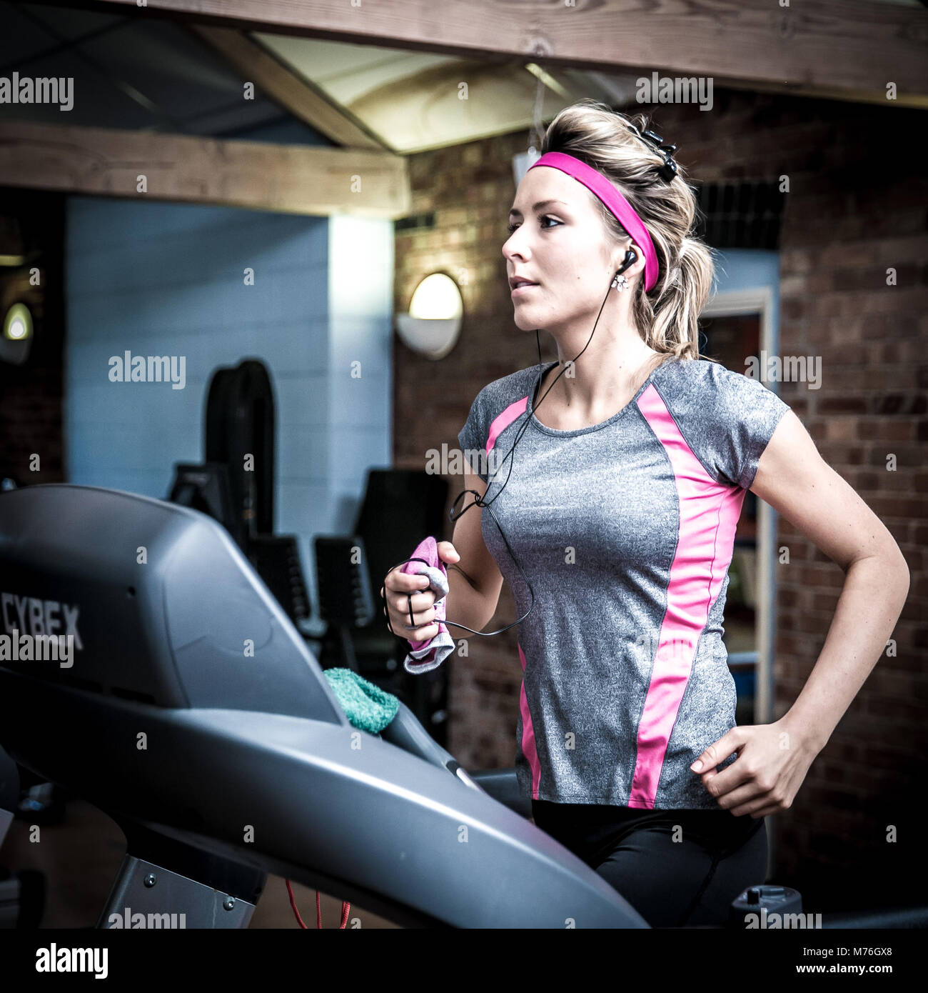 Girl on a treadmill working out in the gym, - Stock Image