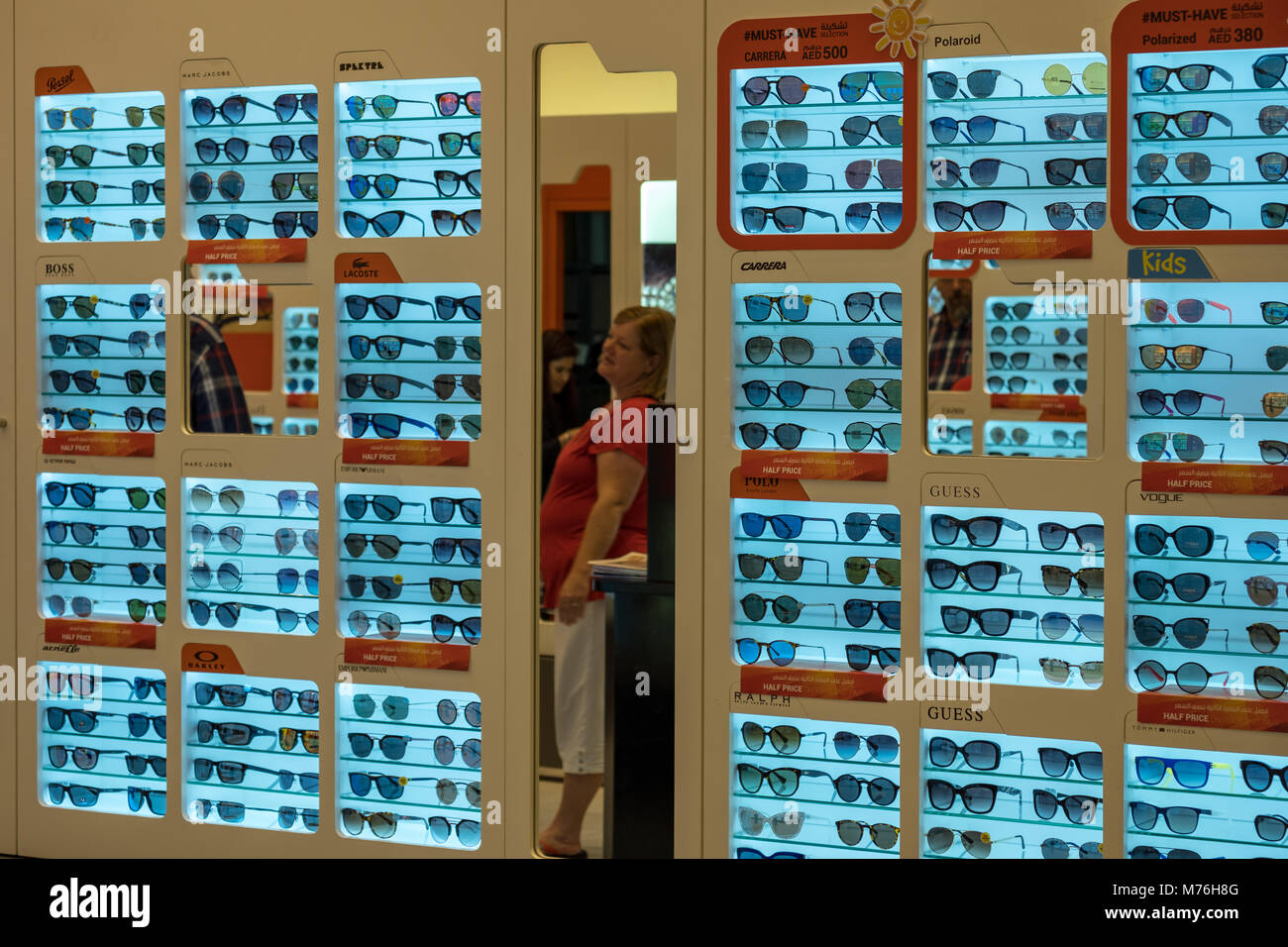 An old woman looking into mirror at Optics store at Yas Mall - Stock Image