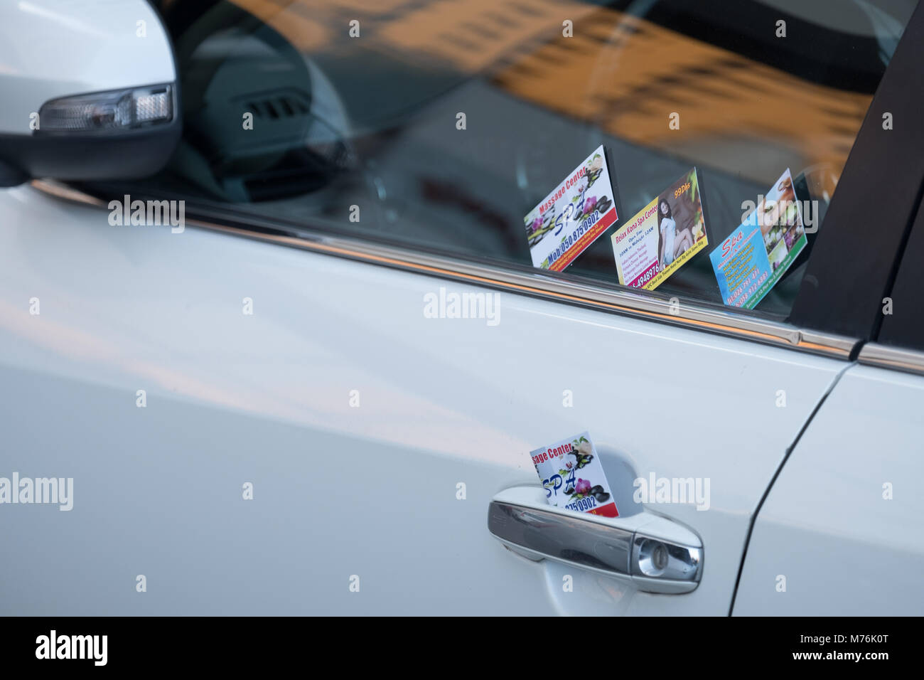Spa and massage visiting cards palced on vehicles' door handle and window glass. - Stock Image