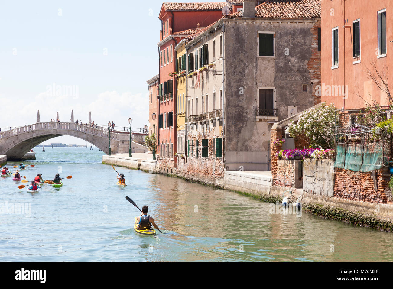 Group of kayakers  in colorful rented canoes or kayaks paddling down Rio de l'Arsenal,  Castello, Venice, Veneto, - Stock Image