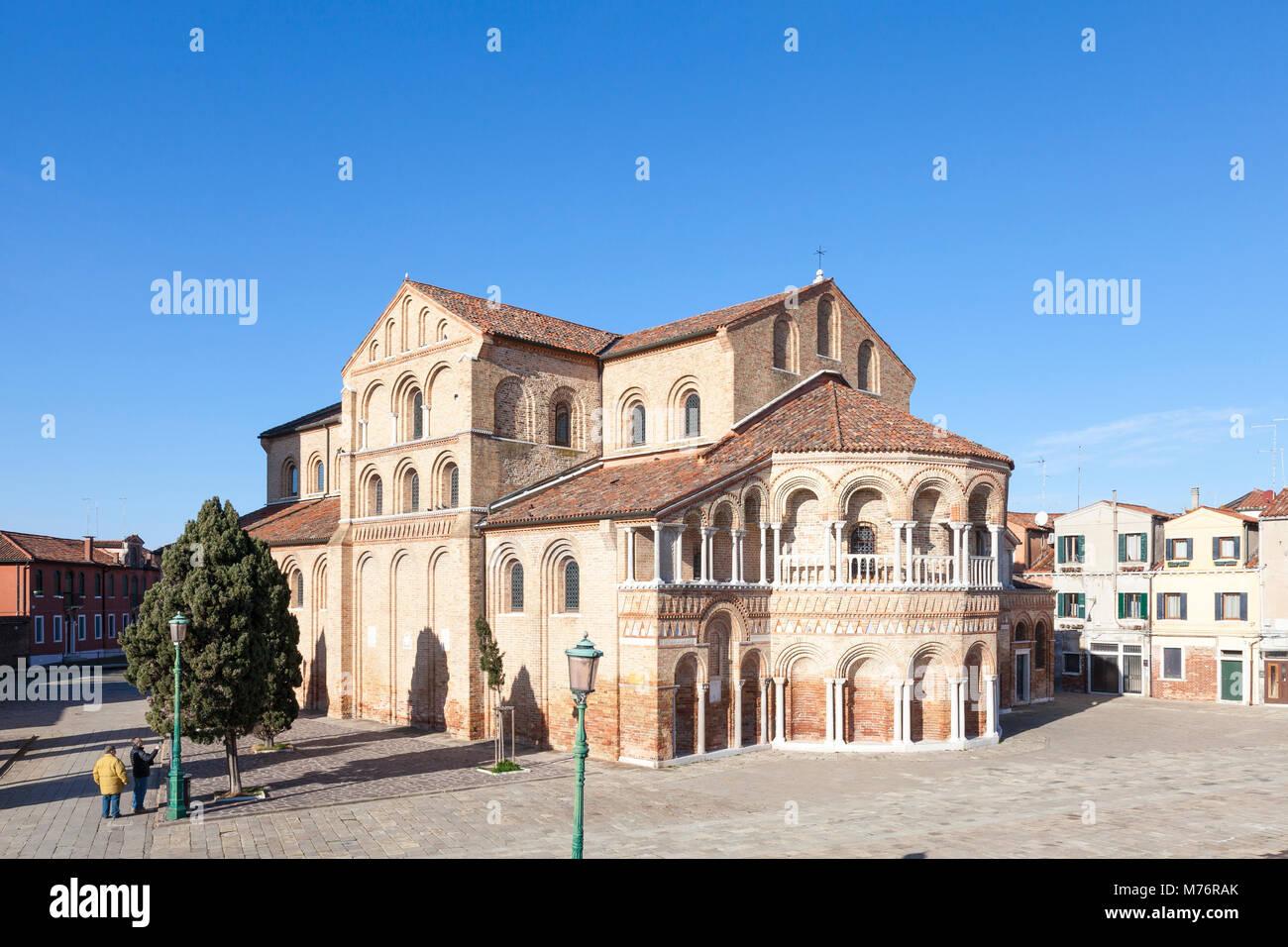 Chiesa dei Santi Maria e Donato, Murano, Venice, Veneto, Italy and Campo San Donata with two tourists sightseeing - Stock Image