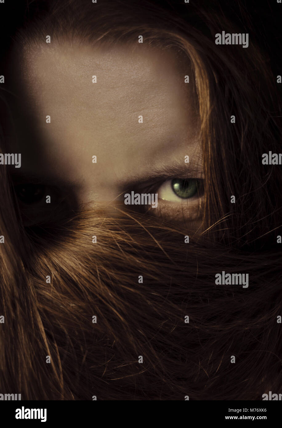 woman hiding behind long hair with only green eye visible - Stock Image