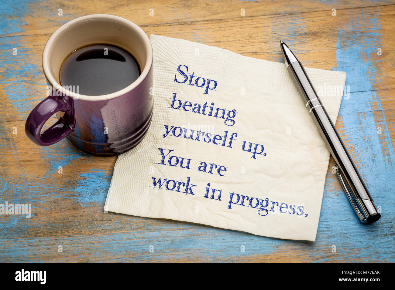 Stop beating yourself up. You are work in progress.  Handwriting on a napkin with a cup of coffee - Stock Image