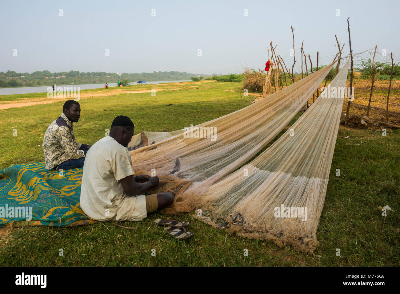 Fishermen repairing their fishing nets on the River Niger, Niamey, Niger, Africa Stock Photo