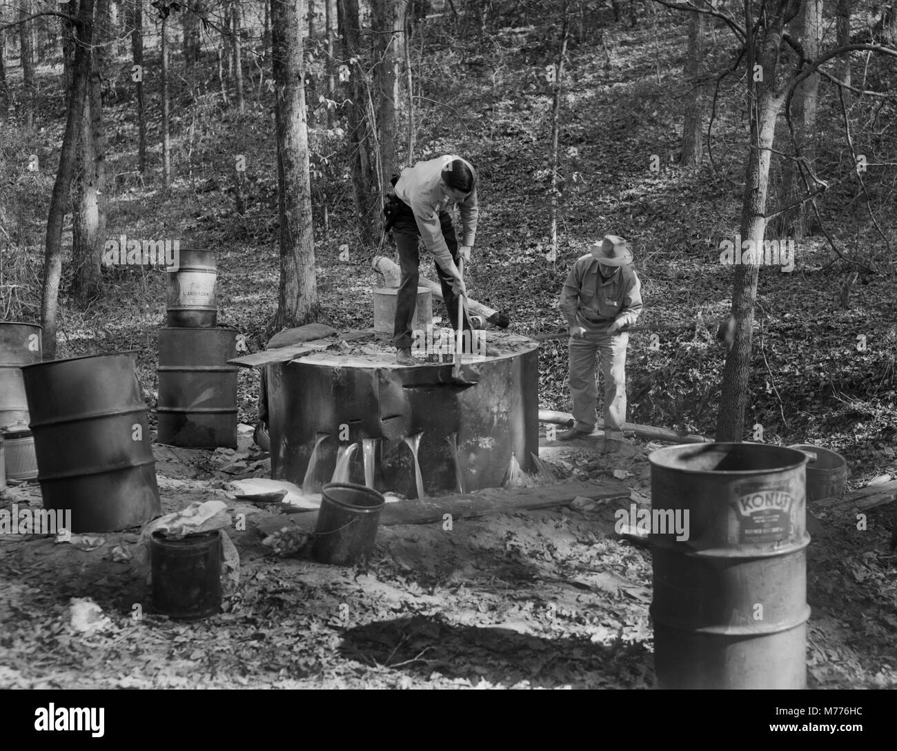 Law enforcement officers destroy a backwoods moonshine still in rural Georgia, ca. 1952. - Stock Image