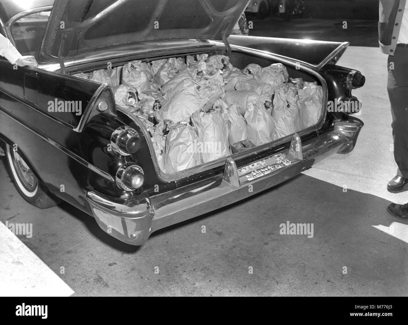 Georgia police display an automobile trunk stuffed with illegal moonshine in the US state of Georgia, ca. 1962. - Stock Image
