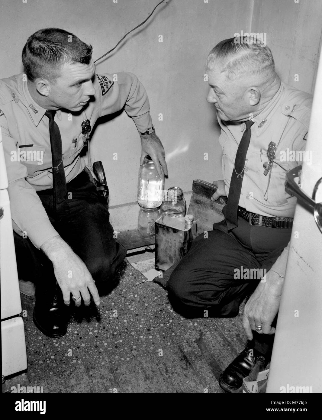 Police in the US state of Georgia examine illegal moonshine hidden beneath a trap door in a rural home, ca. 1962. - Stock Image