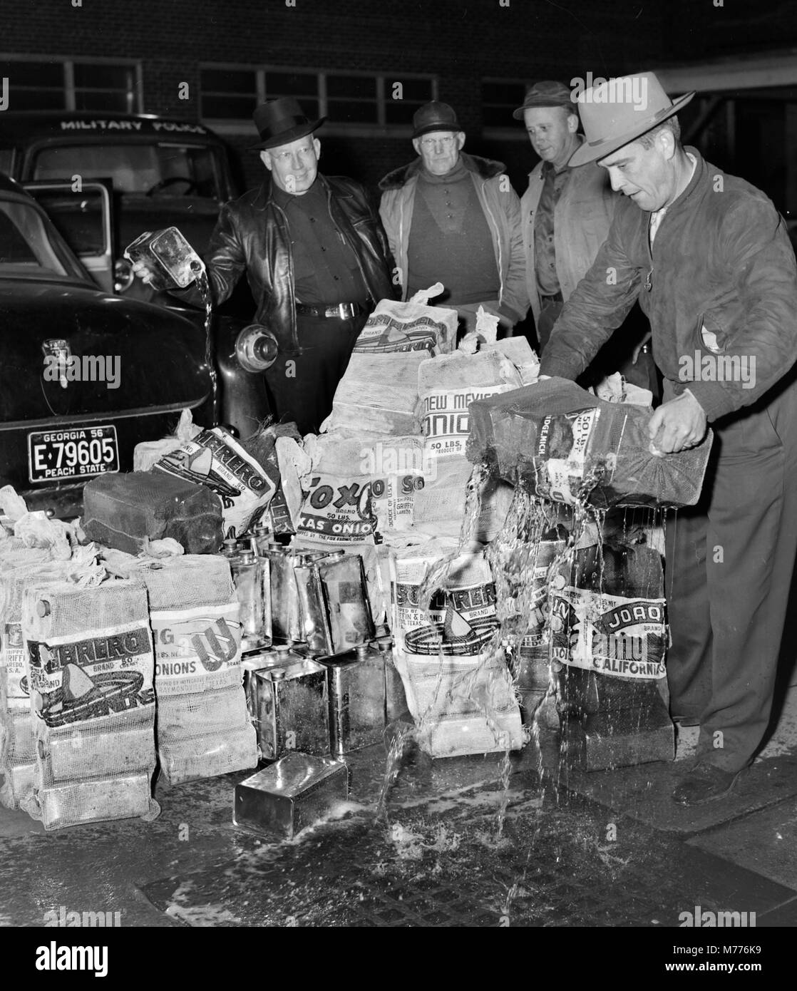Police empty a stash of illegal moonshine liquor into a street drain in the US state of Georgia in 1957. - Stock Image