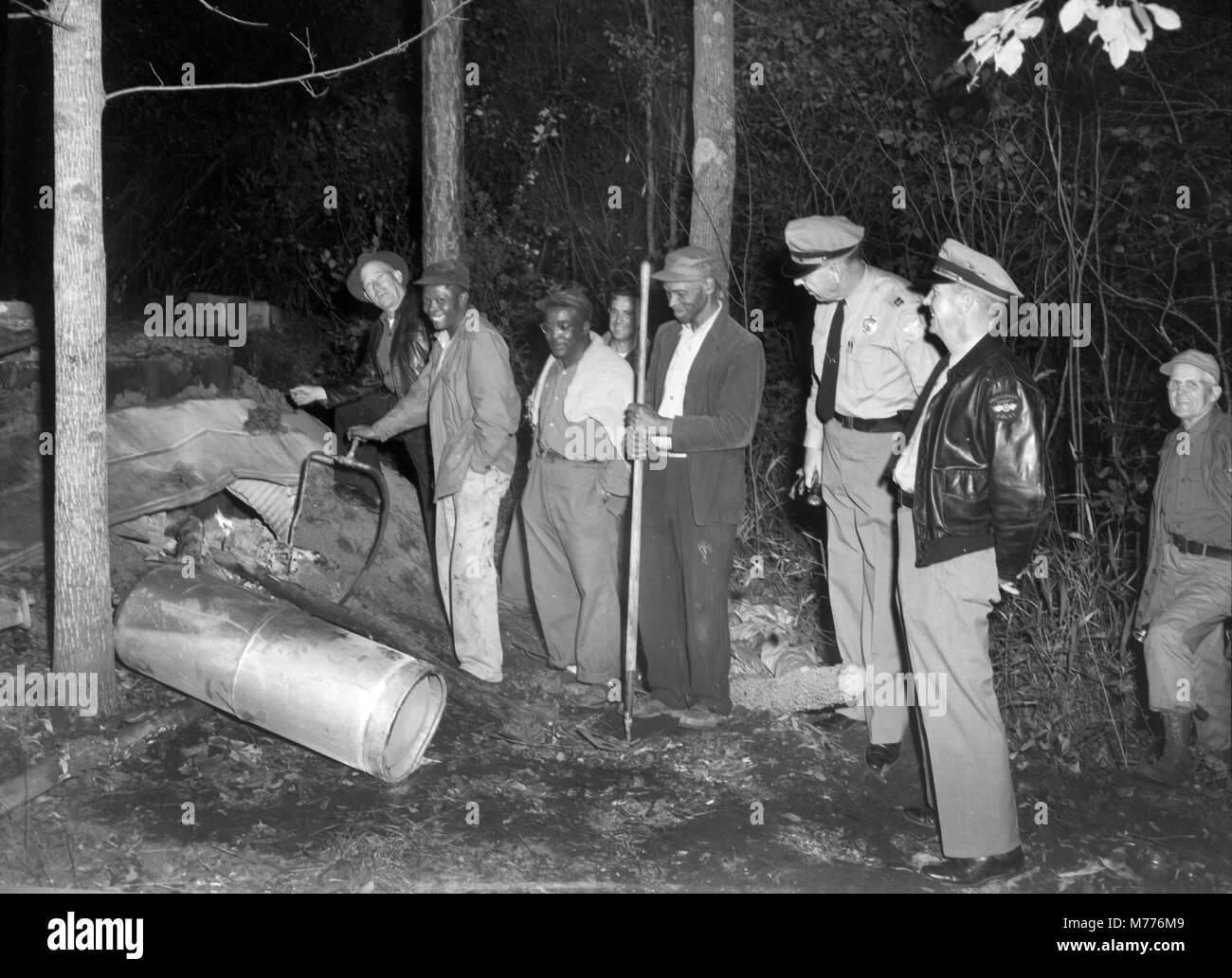 Law enforcement officials investigate the scene of an illegal backwoods moonshine still in rural Georgia, ca. 1955. - Stock Image