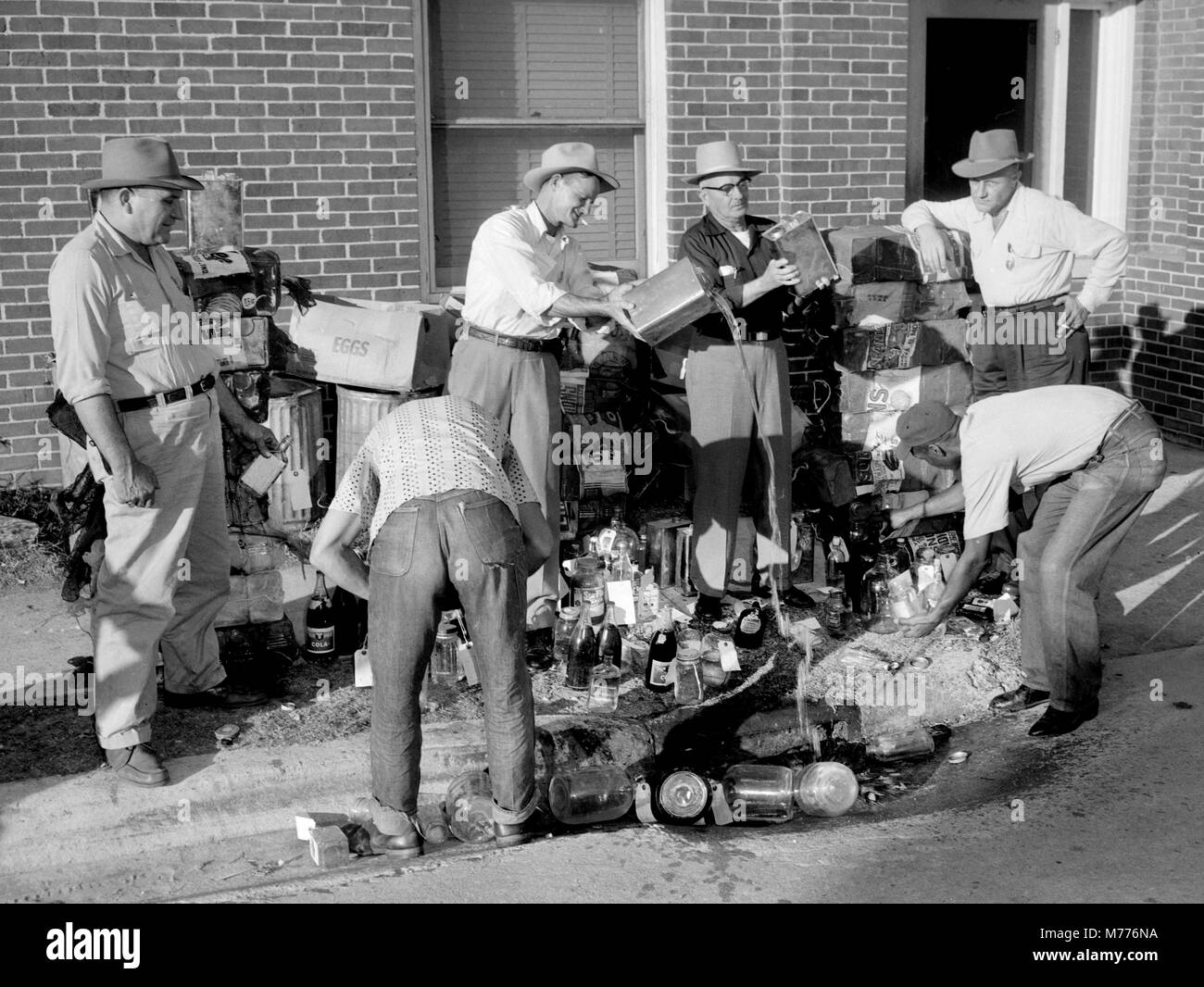 City workers dump illegal moonshine liquor down a storm drain after a raid on still in Georgia, ca. 1955. - Stock Image
