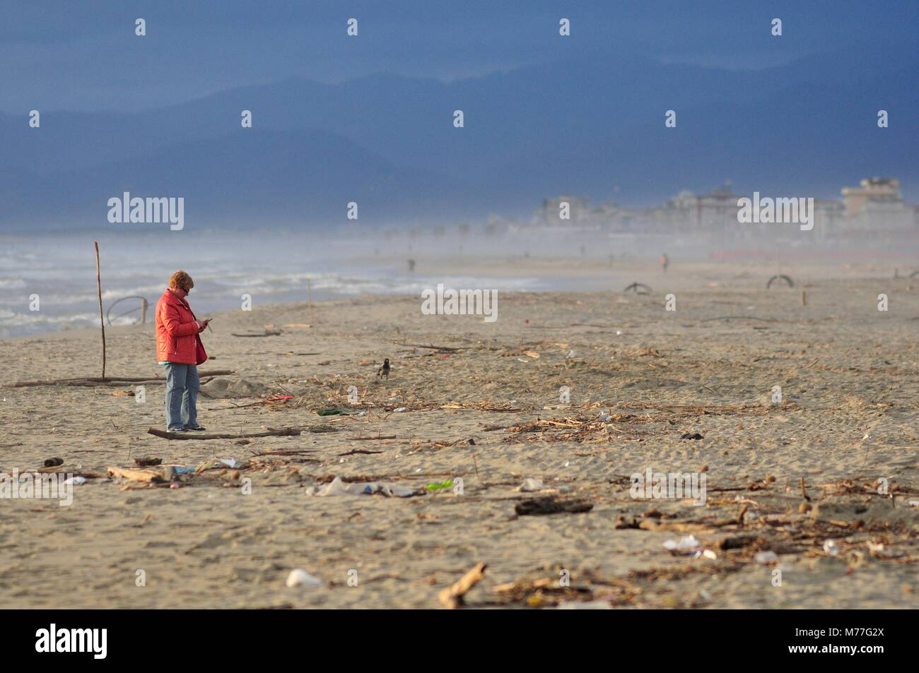 Mature woman using phone in a polluted beach - Stock Image