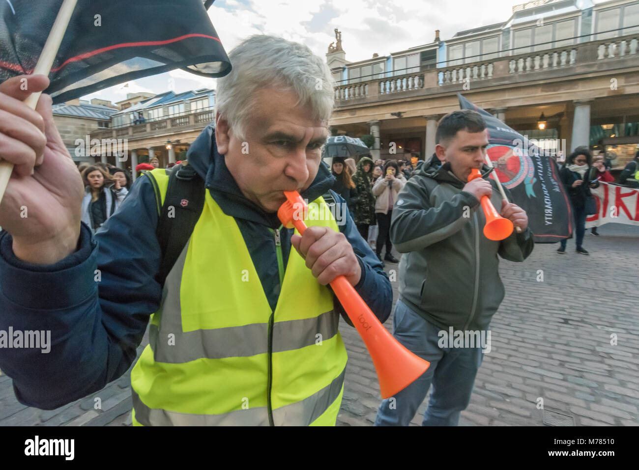 London, UK. 8th March 2018. Cleaners from CAIWU blow vuvzelas at a protest supported by a a large crowd from the Stock Photo