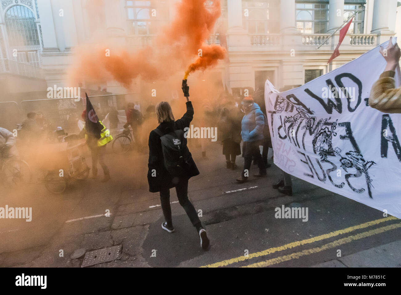 London, UK. 8th March 2018. A woman holds a smoke flare as a large crowd from the London Womens's Strike support Stock Photo