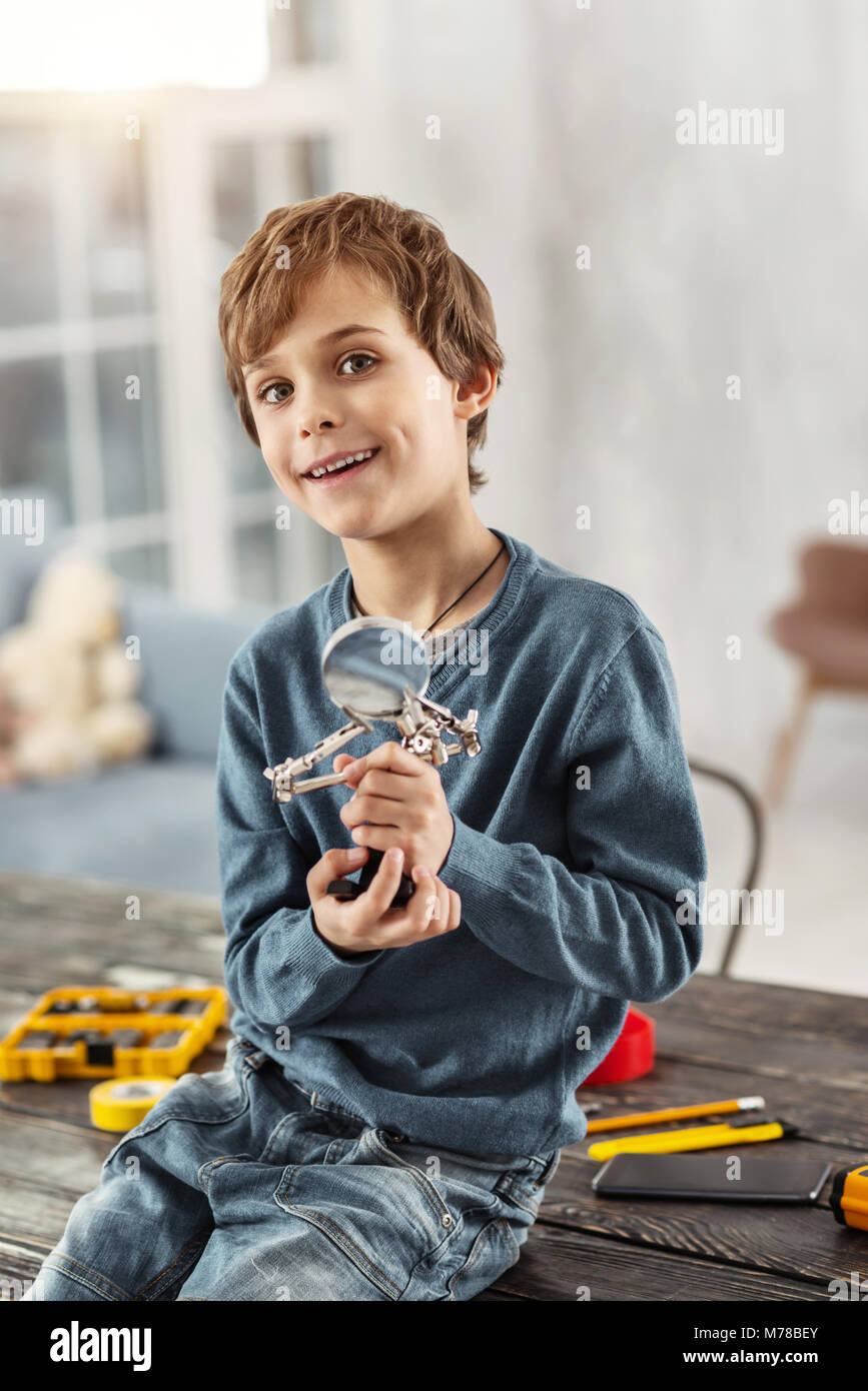 Inspired boy holding a magnifying glass - Stock Image