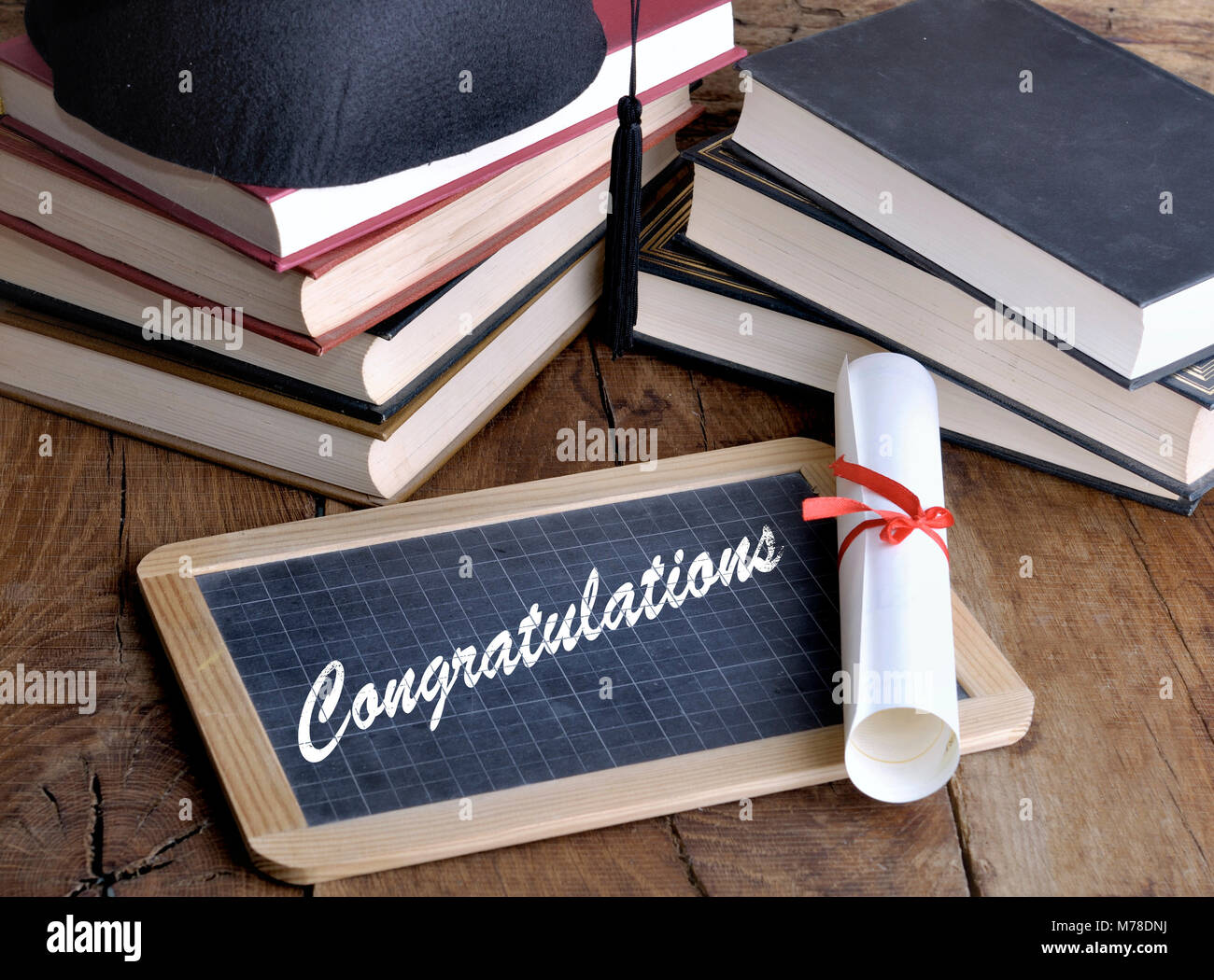 congratulations written on a slate with diploma, books and hat on wooden background - Stock Image