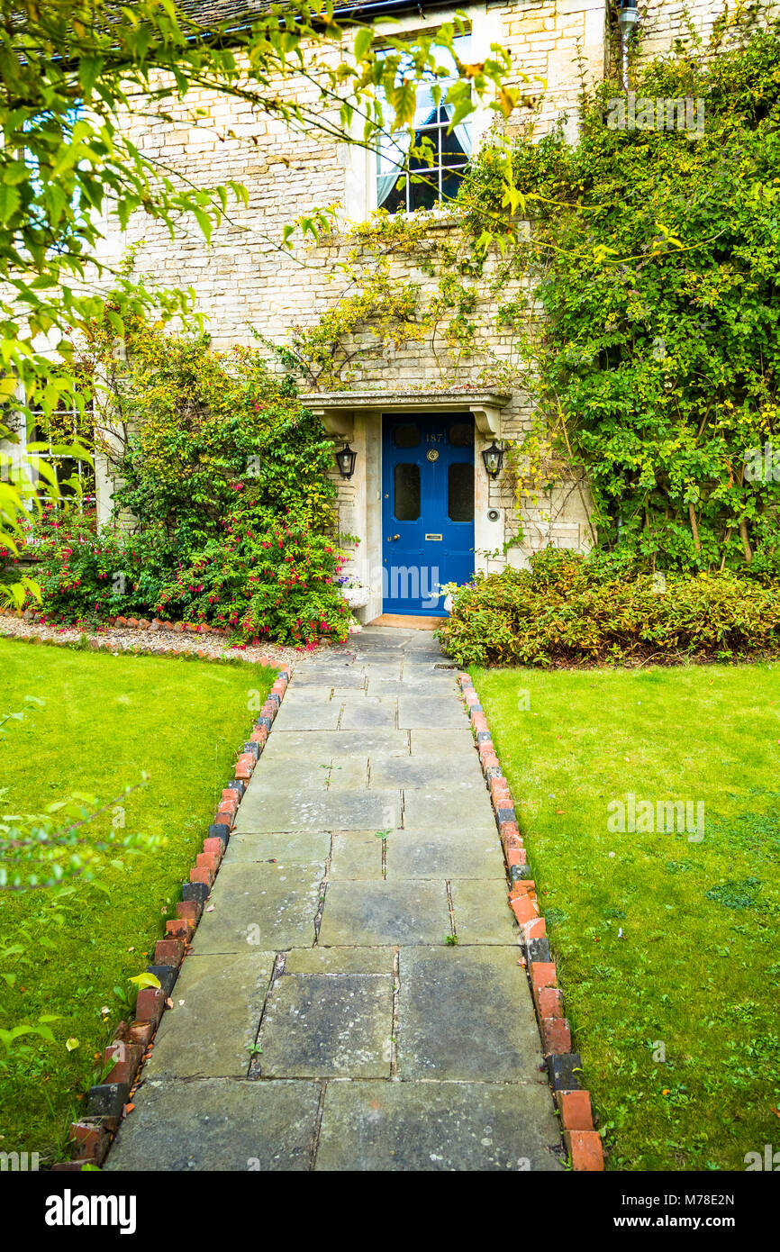 A quiet cottage with a blue door and green grass. - Stock Image