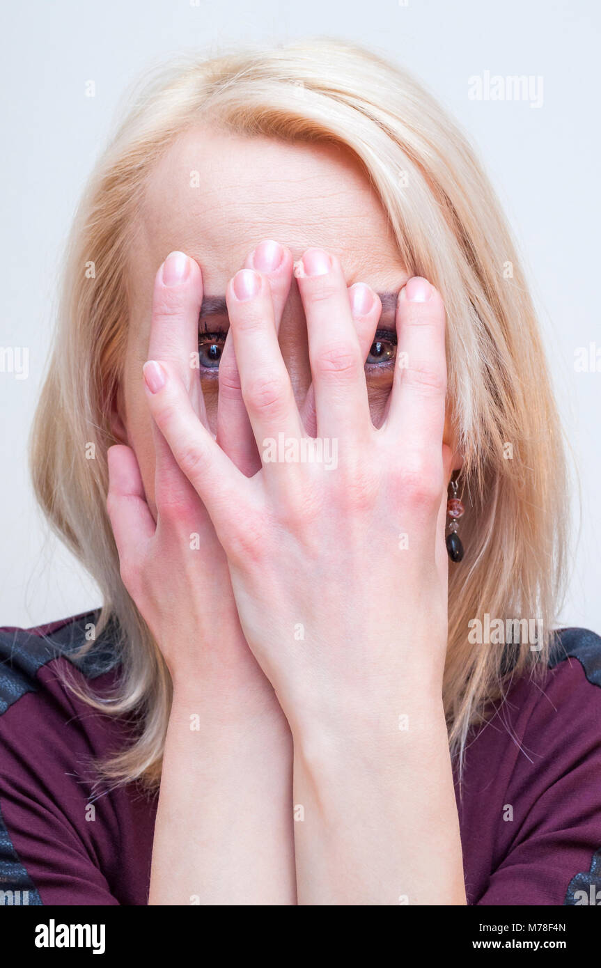 Young blonde woman covering face with palms and looking at camera through fingers. - Stock Image