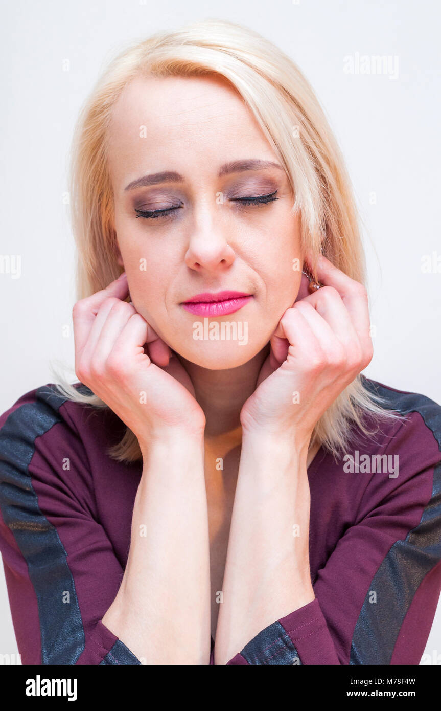 Relaxation and meditation techniques. Young blonde closed eyes woman holding earlobes with fingers. - Stock Image