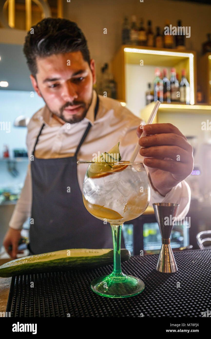 Expert barman is decorating cocktail with cucumber - Stock Image