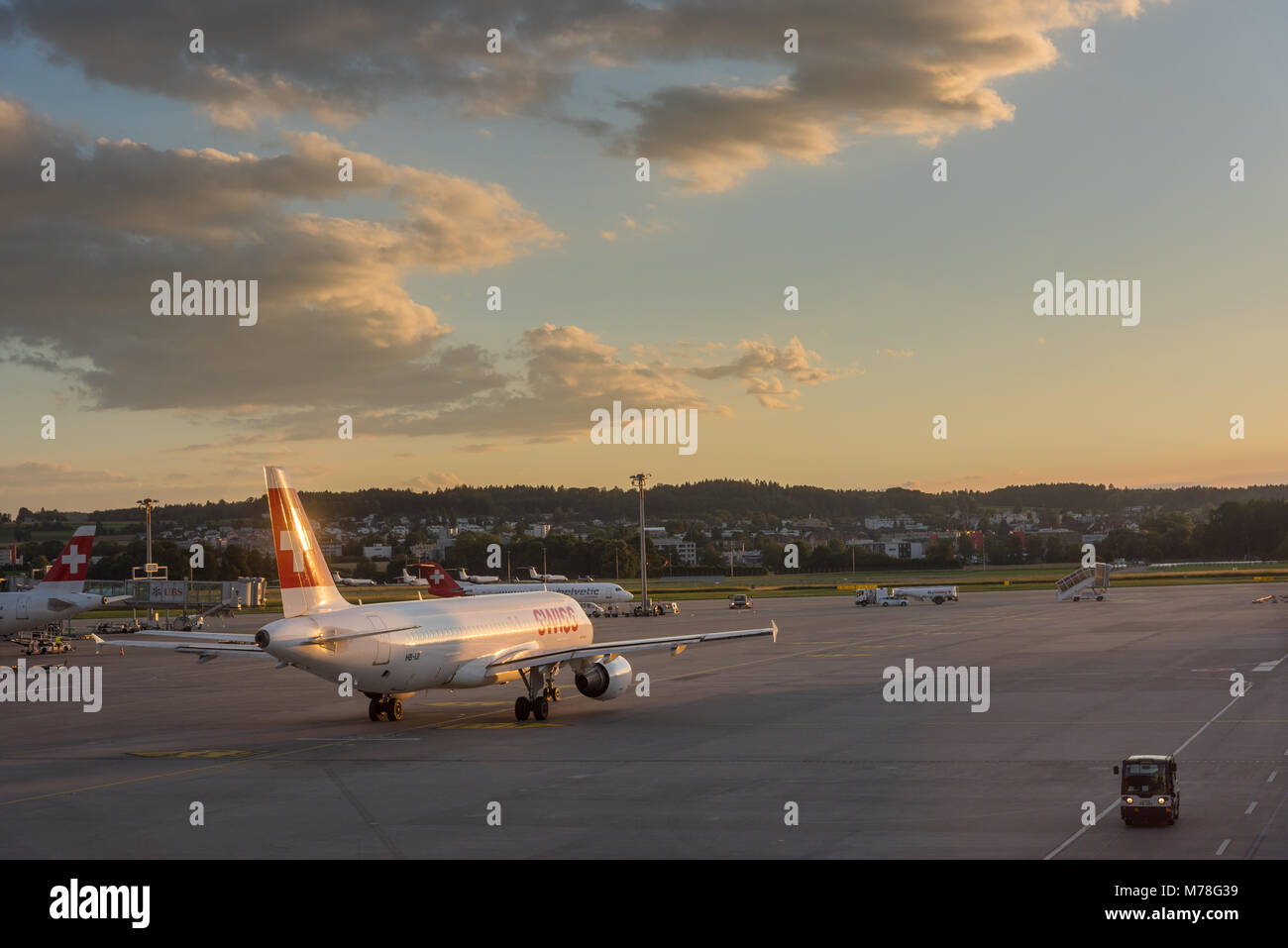 Aircraft departs at Zurich airport at sunset - Stock Image