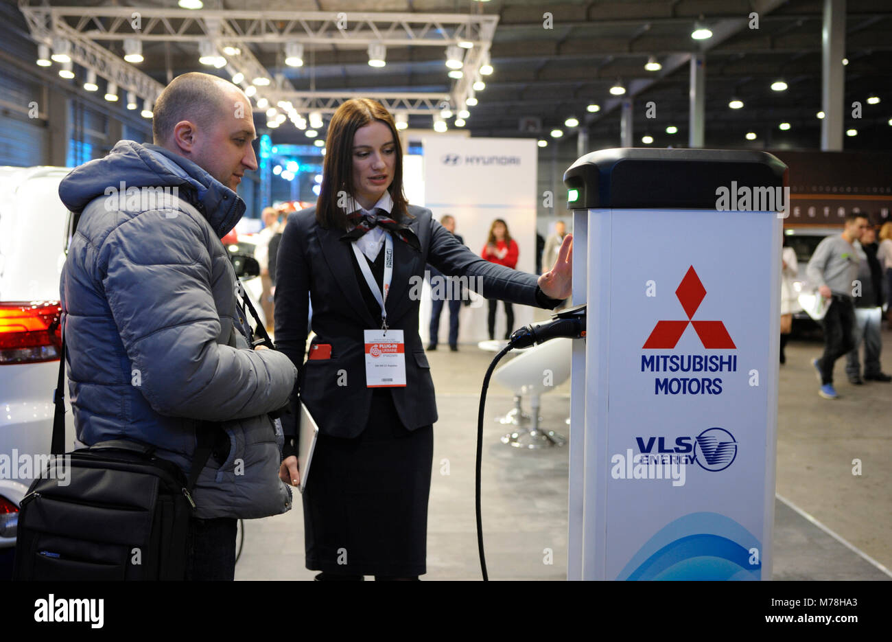 Sales manager explaining how electric car charging station works. Exhibition PLUG-IN UKRAINE 2018. March 2, 2018. - Stock Image
