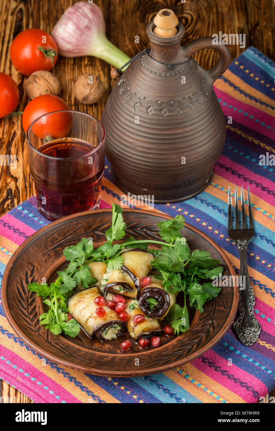 Rolls of fried eggplant with cheese, garlic, cilantro and pomegranate seeds. Gourmet appetizer. Selective focus - Stock Image
