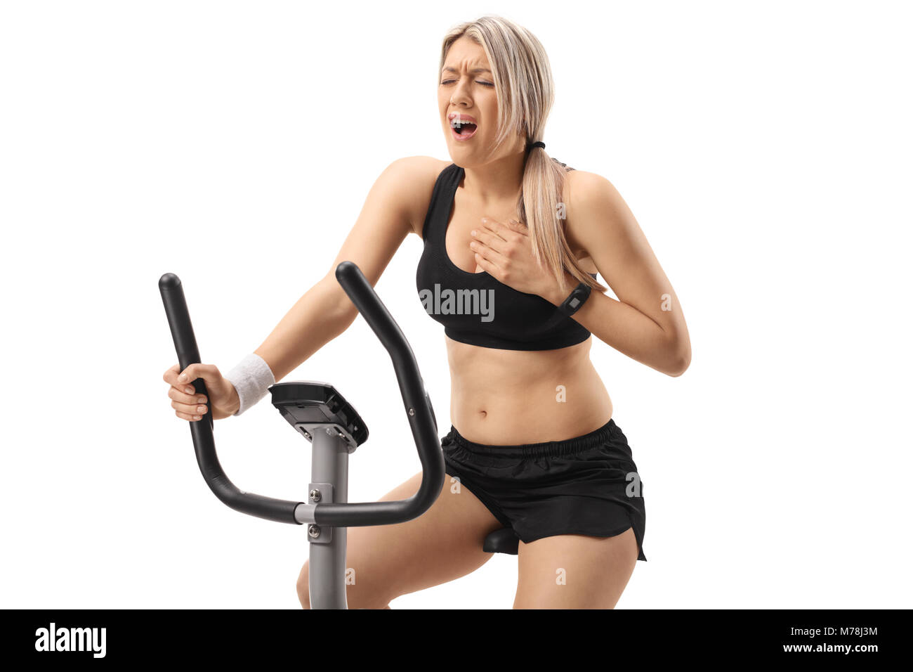 Young woman riding an exercise bike and having a heart attack isolated on white background - Stock Image