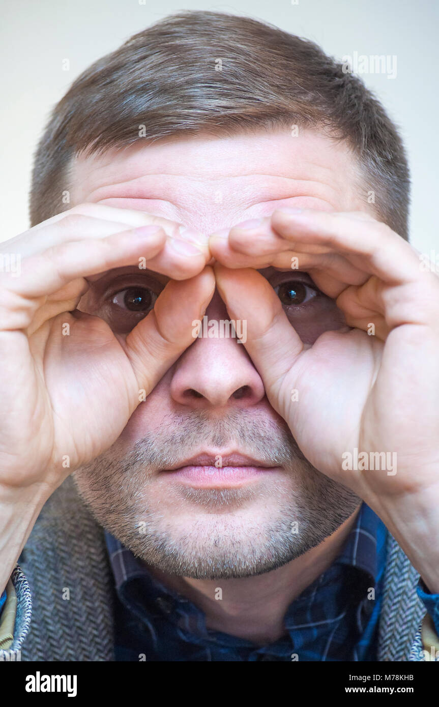 Portrait of young funny playful man holding fingers near eyes in a shape of imaginary binoculars on white background. - Stock Image