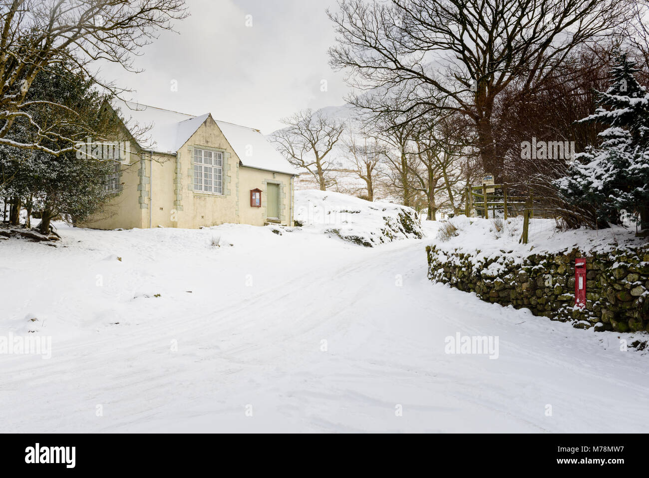 Winter snow covered road past the the Old School Room, now the Village Hall in Buttermere in the English Lake District - Stock Image