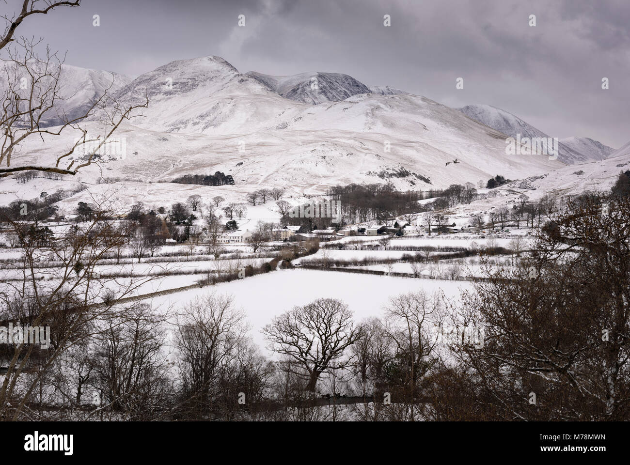 Bleak grey sky over a cold winter view of snow covered Buttermere village with the snowy fells Whiteless Pike and - Stock Image