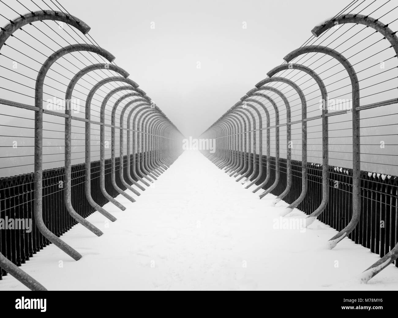 Tunnel like perspective view of anti suicide barriers on bridge in misty winter landscape minimalist snow scene - Stock Image