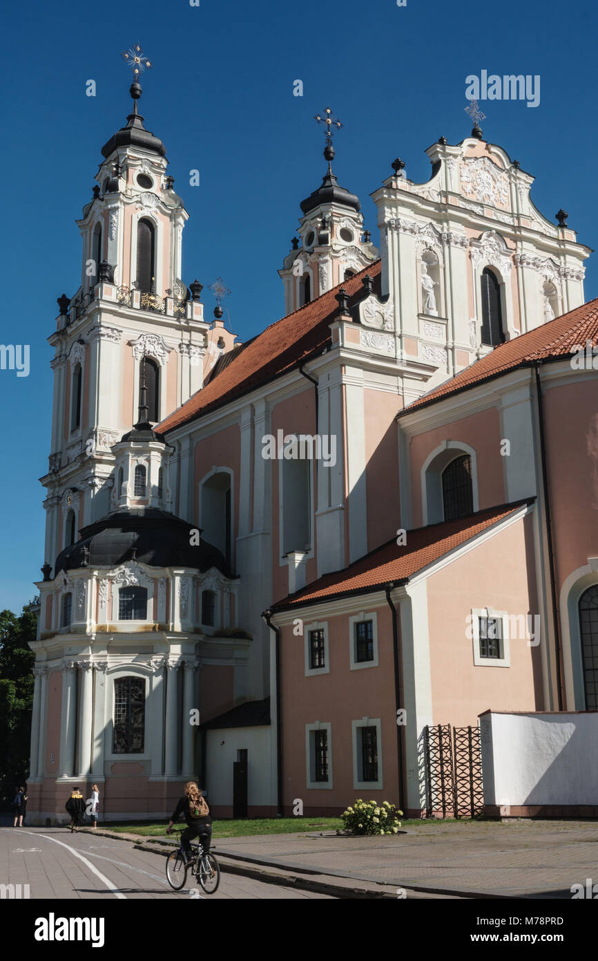 Cyclist passes by strawberry and cream Baroque Church of St Catherine, Old Town, UNESCO Wolrd Heritage Site, Vilnius, - Stock Image