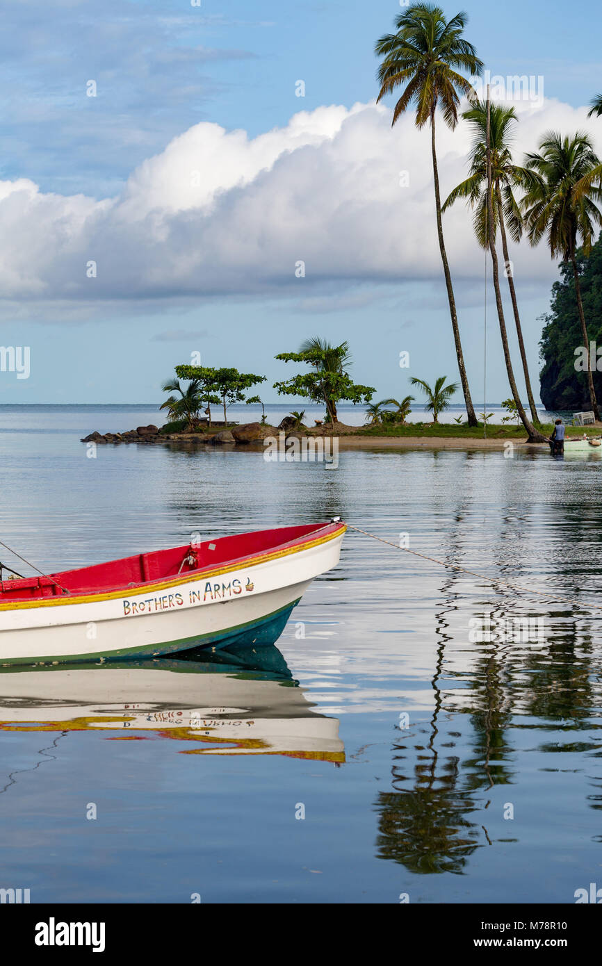 Traditional fishing boat moored at Marigot Bay with tall palms on the small beach in the distance, St. Lucia, Windward - Stock Image