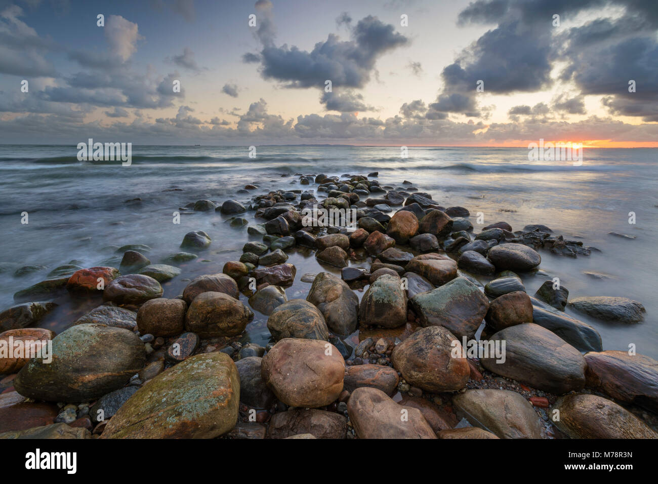 Rock breakwater in sea at sunrise, Munkerup, Kattegat Coast, Zealand, Denmark, Scandinavia, Europe - Stock Image